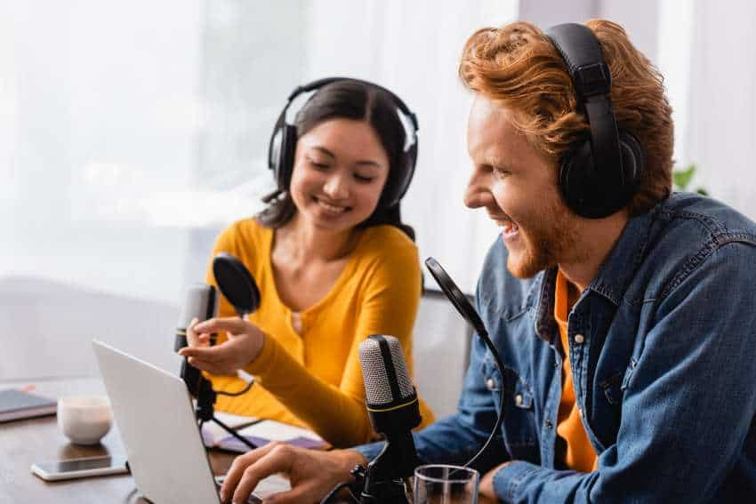Man and Woman doing podcast with headphones